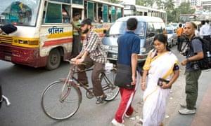 Bike blog :  A cyclist riding trought a traffic jam in a busy street of Dhaka, Bangladesh