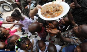 MDG : Malnutrition in Haiti : soldier of the MINUSTAH  gives food to children orphaned by earthquake