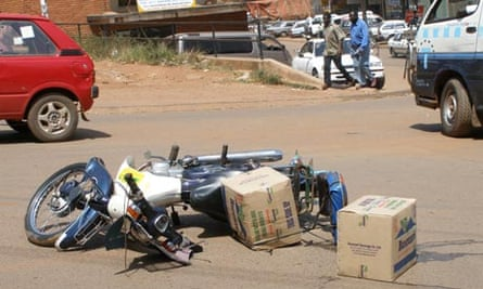 MDG : Road safety in Uganda :  Accident with motorbike carrying bottled water in cartons, Kampala