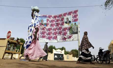 MDG : Mali elections : Women walk by electoral posters in Gao