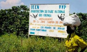 Local woman passing a sign for Virunga National Park, DRC