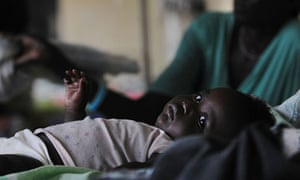 A malaria-infected baby lays in a bed in