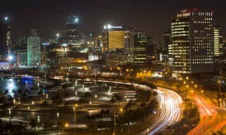 MDG : Africa ghost town : city skyline and promenade stand illuminated at night in Luanda, Angola