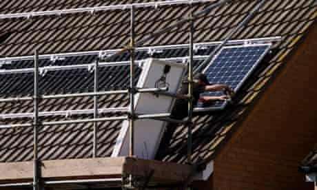 Green deal : Engineers fit solar panels to the roof of a domestic property, Peterborough