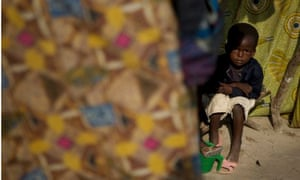 A boy sits inside a makeshift shelter made from pieces of cloth in Bangui, Central African Republic