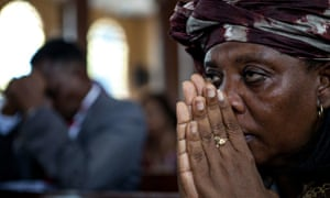A woman prays for victims of the Ebola v