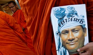 MDG : A Buddhist monk holds the portrait of a detainee during a protest in central Phnom Penh