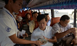 MDG : A Cambodian man buys a ticket in a City bus in Phnom Penh