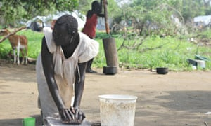 MDG a woman grinds grain in South Sudan