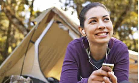 Woman listening to MP3 player outside tent