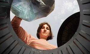 A householder puts rubbish in a bin