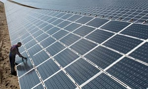 A worker tends to the world's largest solar plant in Germany