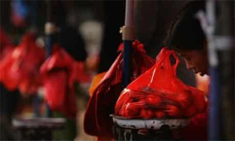 A market vendor weighs tangerines in a plastic bag in Beijing