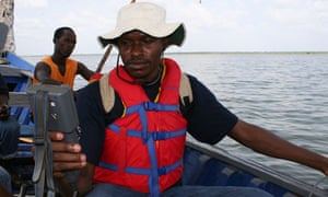 An Earthwatch researcher is pictured taking the water temperature at Lake Volta in Ghana as part of this scientific study