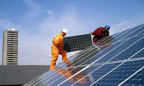 Engineers fitting solar panels to a roof at Silvertown Solar Village, Docklands, London