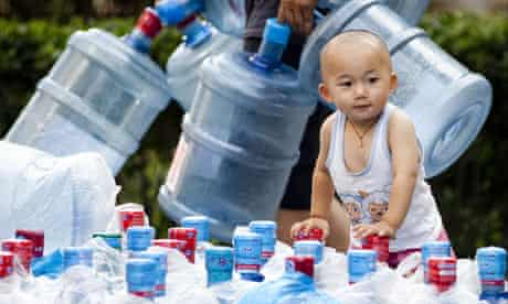 Children of the revolution ... water bottles are brought in to a housing complex in Beijing, China.