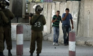 Palestinians pass near an Israeli checkpoint in the West Bank