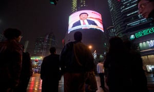 People watch a giant TV showing Xi Jinping at the 18th Communist Party Congress