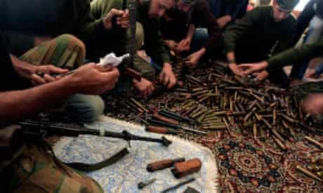 Syrian rebels clean their weapons and check ammunition at their base on the outskirts of Aleppo