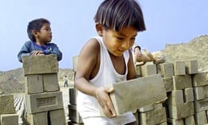 A three-year-old Peruvian boy lifts a brick in an informal brickyard in a shantytown in Lima
