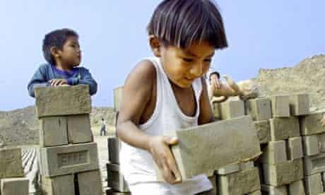 A three-year-old Peruvian boy lifts a brick in an informal brickyard in a shantytown in Lima
