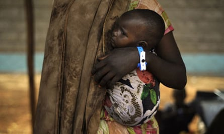 A Somali refugee holds her baby following her registration at the Dadaab refuge complex.