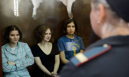 Members of Pussy Riot sit in a glass cage during their trial in Moscow