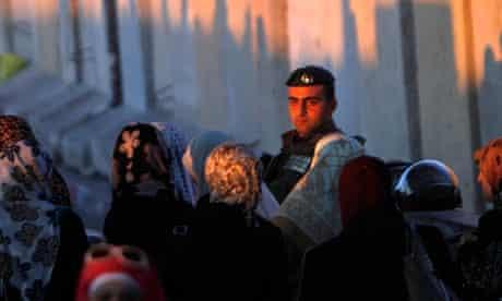 Palestinian women walk past an Israeli soldier