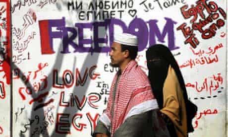 Egyptians walk past graffiti in Cairo