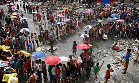 Victims of Typhoon Haiyan queue for food and water in Tacloban city