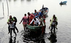 Boat guides carry people through oil-polluted water in Nigeri'a Ogoniland