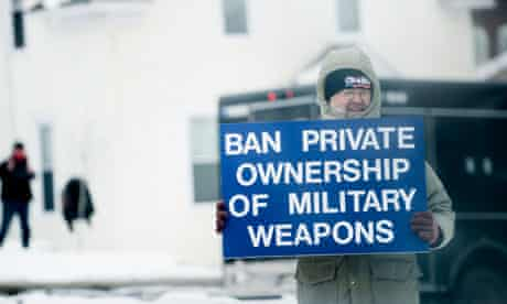 A man holds up a gun control sign as President Obama's motorcade passes in Minneapolis, Minnesota