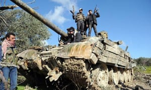 Syrian rebel fighters stand on a Soviet-made tank abandoned by government forces.