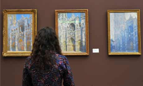 woman looks at paintings