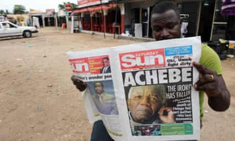 A Nigerian reads a newspaper featuring a headline on Chinua Achebe's death on 22 March