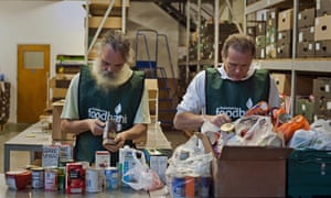 Volunteers sort through donations of food at a food bank