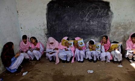 Pakistani schoolgirls attend class at a makeshift school near Lahore, Pakistan