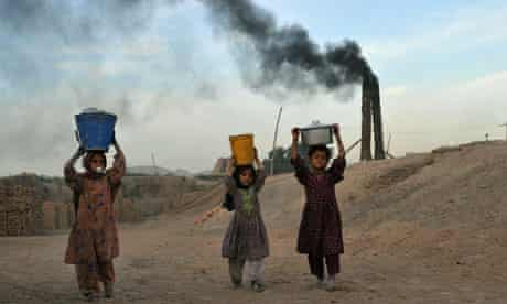 TOPSHOTS Afghan children carry coal for