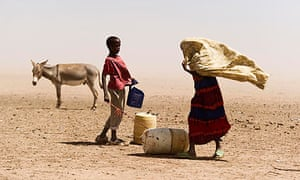 Two people and a donkey stand near water containers in Somalia
