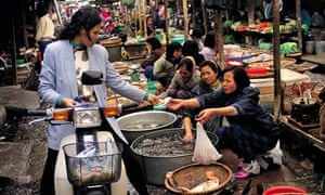 A shopper buys fish at a market in Hanoi