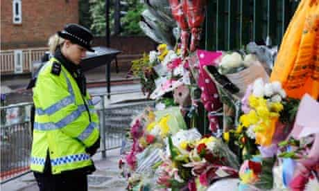 A policewoman in Woolwich looks at flowers left by members of the public where Lee Rigby was killed