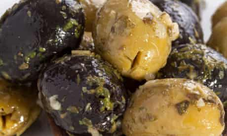 Green and black olives on wooden spoon