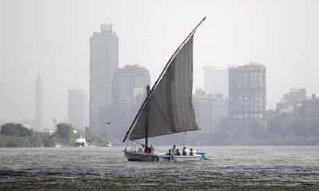A man with his family travel on a home boat near garbage plants in the Egyptian Nile River in Cairo