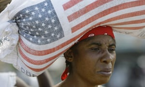 A Haitian woman carries a bag of rice donated by USAid