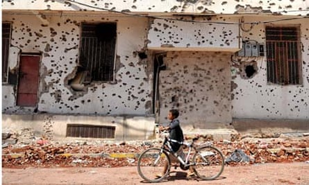 A boy walks past a bullet-scarred building in the Yemeni capital, Sana'a.