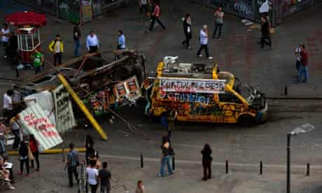 A damaged TV broadcasting van and a mini bus at Taksim Square