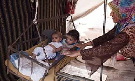 A Syrian refugee woman rocks her children