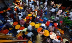 Vendors sell flowers at a wholesale flower market in Mumbai, India