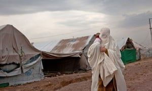 A woman carries a child as she walks through the Jalozai IDP camp in Nowshera, Pakistan