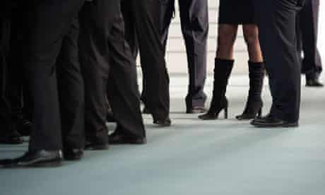 A woman stands surrounded by men